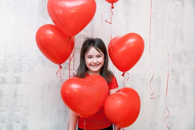Lächelndes mädchen, das unter roten heliumherzförmigen luftballons auf einem weißen hintergrund steht