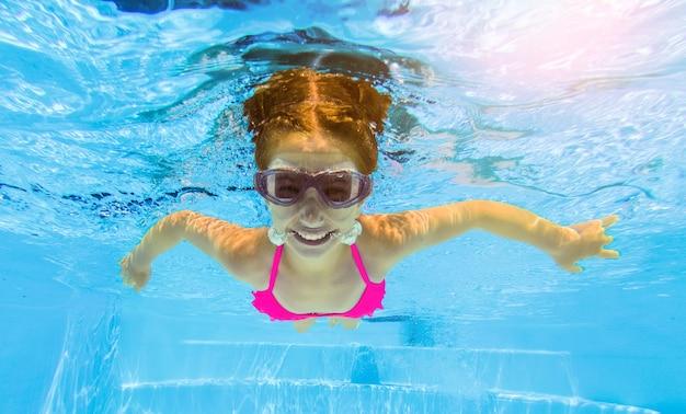 Lächelndes mädchen, das unter wasser im pool schwimmt