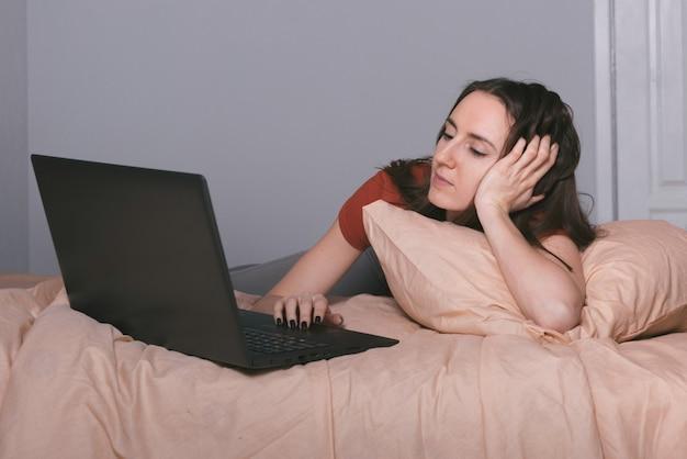 Lächelndes mädchen, das von zu hause aus am laptop arbeitet, während es auf dem bett liegt