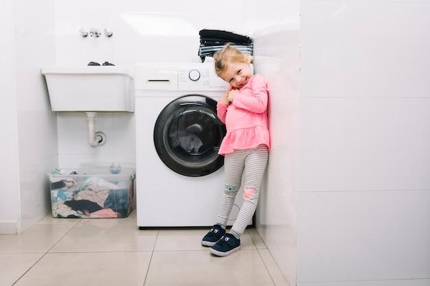 Lächelndes mädchen, das vor waschmaschine steht