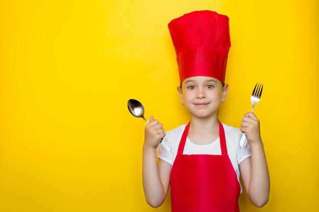Lächelndes mädchen im anzug eines roten chefs, der einen löffel und eine gabel, einladend zum abendessen auf gelb hält