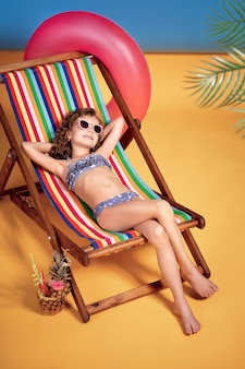 Lächelndes mädchen im badeanzug und in der sonnenbrille, die im regenbogenliegestuhl mit gekreuzten beinen und im sonnenbad liegen