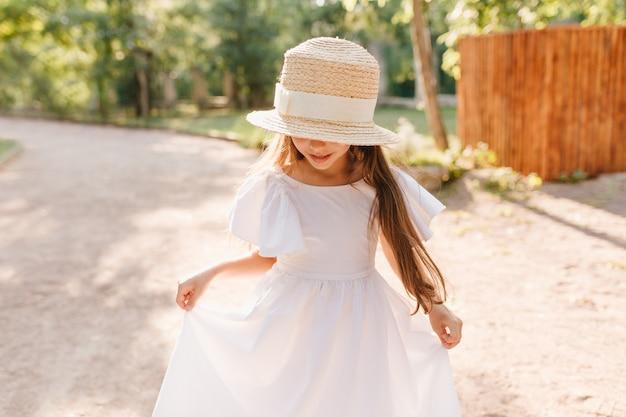 Lächelndes mädchen im großen strohhut betrachtet ihre füße während des tanzes im park. kleine dame trägt stilvollen bootsfahrer, der mit weißem kleid spielt und neue kleidung genießt.