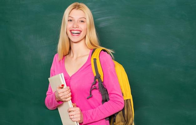 Lächelndes mädchen im klassenzimmer mit tasche.