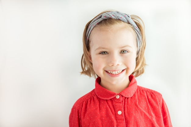 Lächelndes mädchen im roten hemd und in den schönen augen. porträt