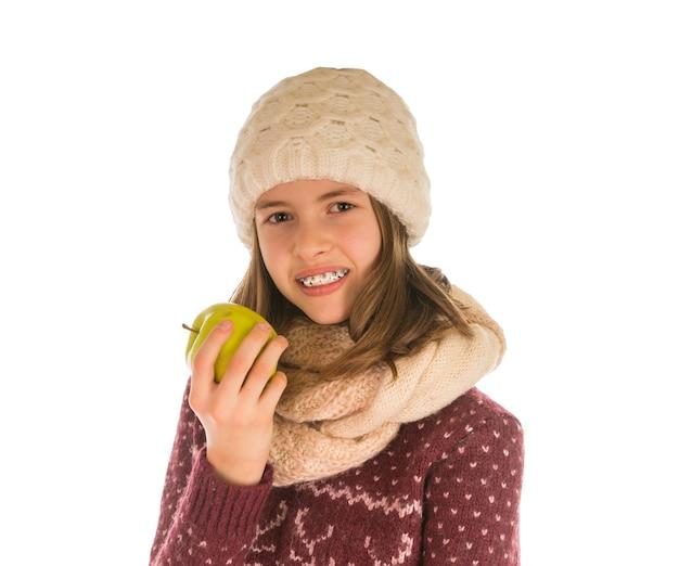 Lächelndes mädchen im warmen pullover, in der mütze, im schal und in den handschuhen, die einen apfel essen, der auf weiß isoliert wird