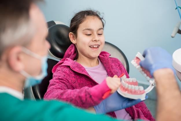 Lächelndes mädchen im zahnarztstuhl erziehend über das korrekte zähneputzen durch ihren pädiatrischen zahnarzt