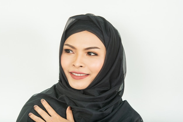 Lächelndes mädchen in der hijab bedeckung schön mit glück und farbwand