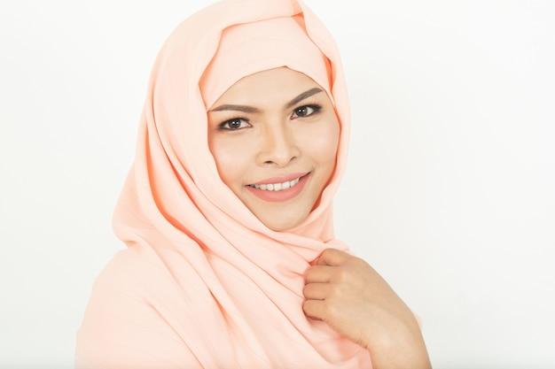 Lächelndes mädchen in der hijabbedeckung schön mit glück und farbwand