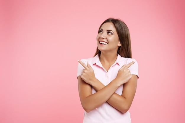 Lächelndes mädchen in der rosa sportbekleidung, die mit den händen über weg schaut