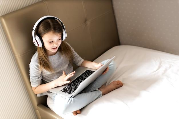 Lächelndes mädchen in drahtlosen kopfhörern mit ihrem laptop auf dem bett zu hause