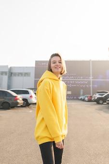 Lächelndes mädchen in einem gelben kapuzenpulli auf dem parkplatz