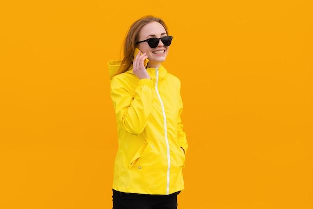 Lächelndes mädchen in einer gelben jacke spricht am telefon einzeln auf orangem hintergrund