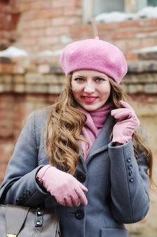 Lächelndes mädchen in grauem mantel und rosa baskenmütze