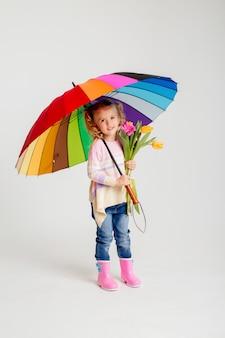 Lächelndes mädchen in passendem rosa hemd und regenstiefeln, die regenbogenschirm auf weißem hintergrund halten