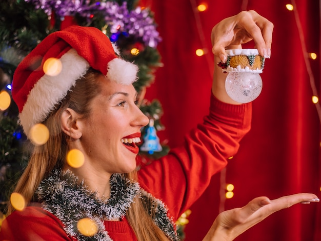 Lächelndes mädchen in sankt hut mit spielzeug. weihnachtsbaum wand