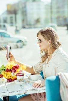 Lächelndes mädchen macht ein selfie, das auf der terrasse des cafés sitzt