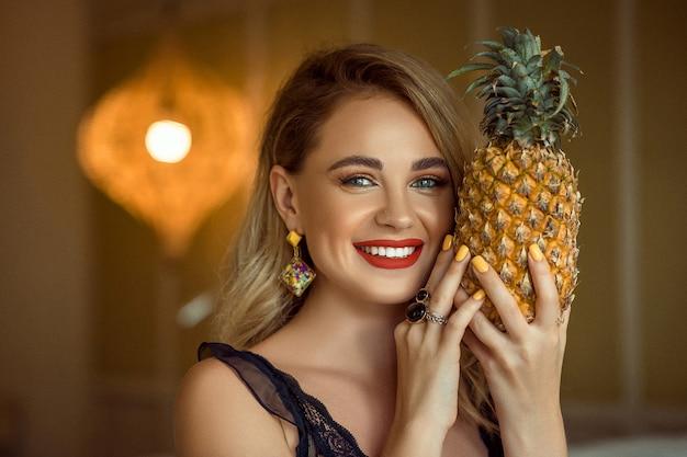 Lächelndes mädchen mit abend bilden das tragende zubehör, das ananas, abschluss aufwirft und hochhält.