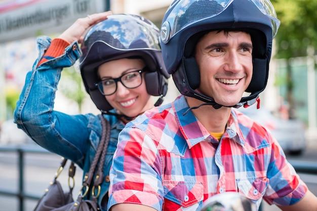 Lächelndes mädchen mit brille, die auf soziussitz des rollers sitzt