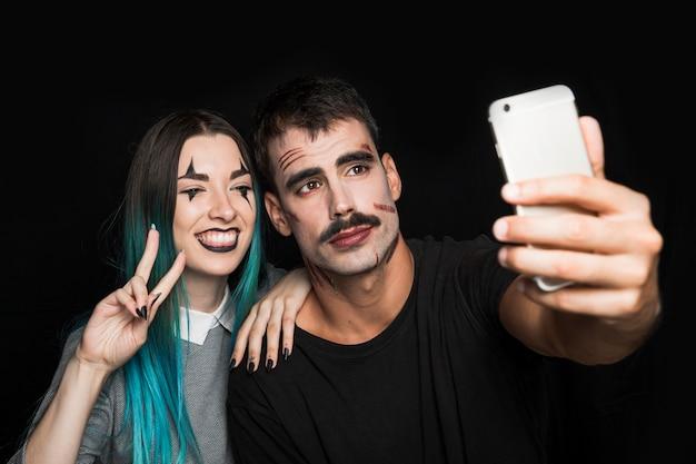 Lächelndes mädchen mit dem mann, der selfie am telefon nimmt