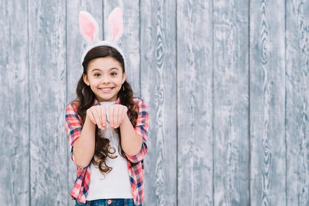 Lächelndes mädchen mit den häschenohren, die wie kaninchen gegen grauen hölzernen schreibtisch aufwerfen