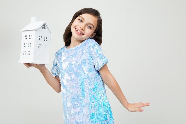 Lächelndes mädchen mit einem modell zu hause auf einem weißen mit kopienraum. immobilien