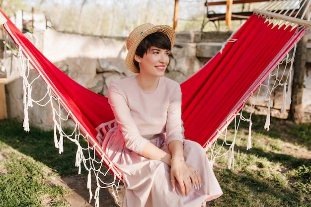 Lächelndes mädchen mit eleganter maniküre, die langes retro-kleid trägt, das draußen im sonnigen tag ruht