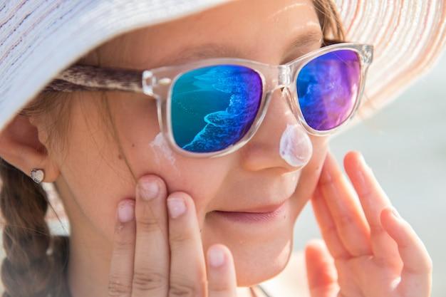 Lächelndes mädchen mit hut schmiert schützende gesichtscreme am strand