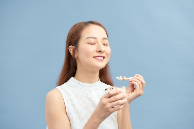 Lächelndes mädchen mit joghurt-haferflocken-nachtisch zum frühstück.