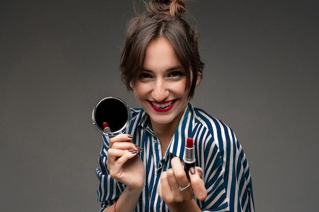 Lächelndes mädchen mit rotem lippenstift und einem spiegel an einer dunklen wand