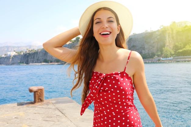 Lächelndes mädchen mit rotem sommerkleid und hut in sorrent, süditalien