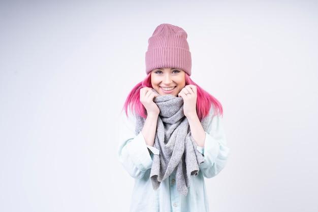 Lächelndes mädchen mit schal und rosafarbenem hut