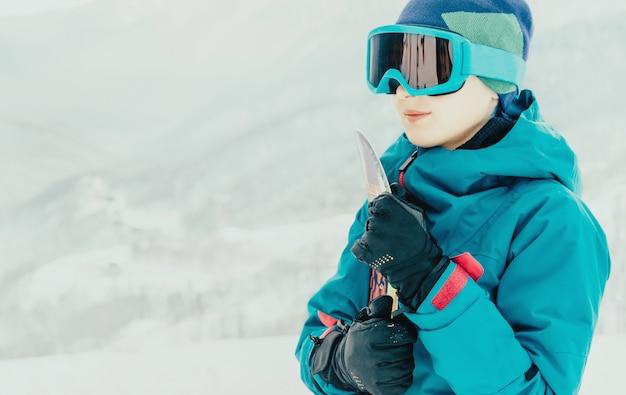 Lächelndes mädchen mit snowboard im winter