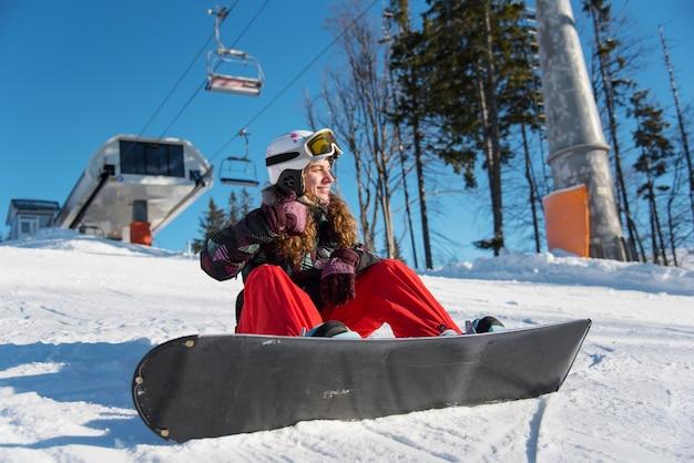 Lächelndes mädchen mit snowboard