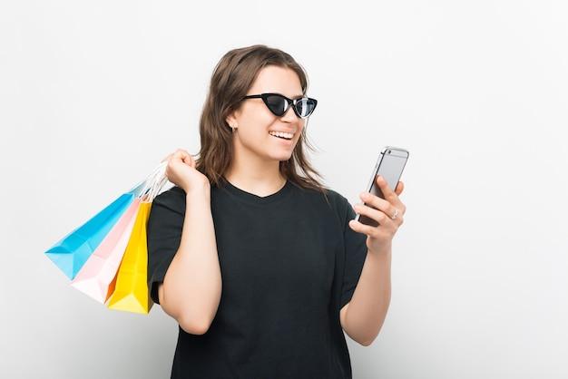 Lächelndes mädchen mit sonnenbrille bestellt etwas online über ihr telefon.