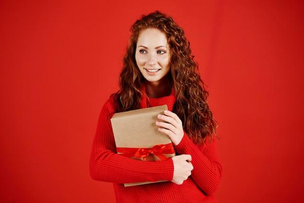 Lächelndes mädchen mit weihnachtsgeschenk, das kopienraum betrachtet