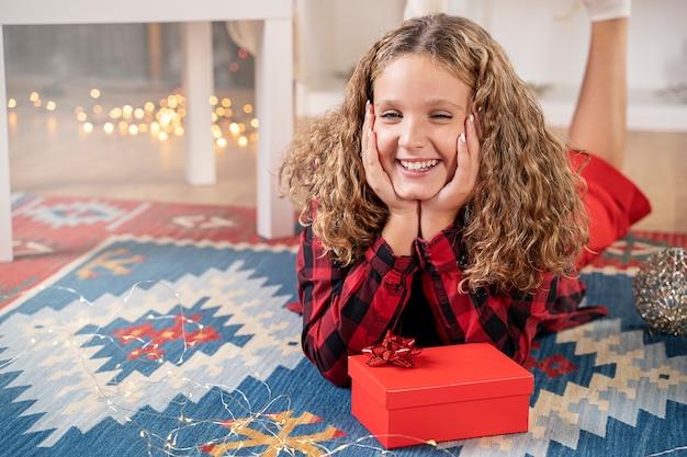 Lächelndes mädchen mit weihnachtsgeschenkbox in der weihnachtszeit