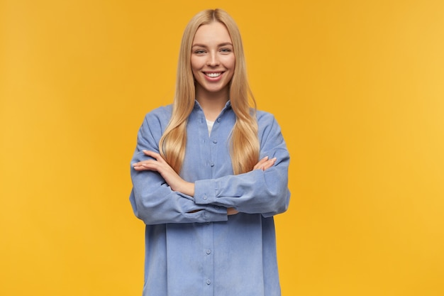 Lächelndes mädchen, positiv aussehende frau mit blonden langen haaren. blaues hemd tragen. menschen- und emotionskonzept. hält die arme auf einer brust verschränkt. beobachten in der kamera, isoliert über orange hintergrund