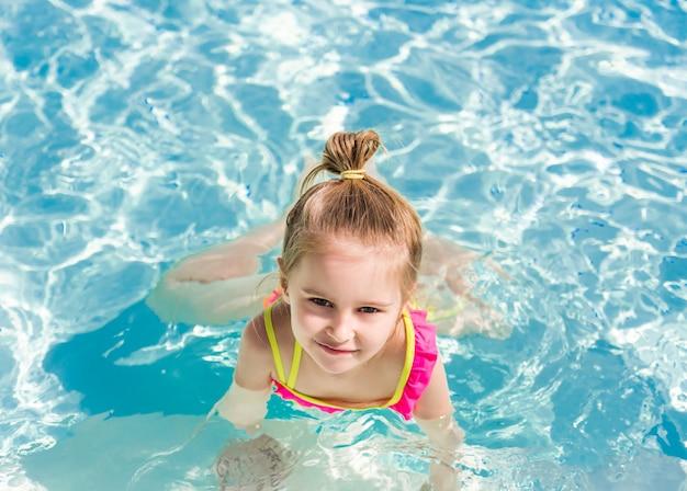 Lächelndes mädchen schwimmen zum pool
