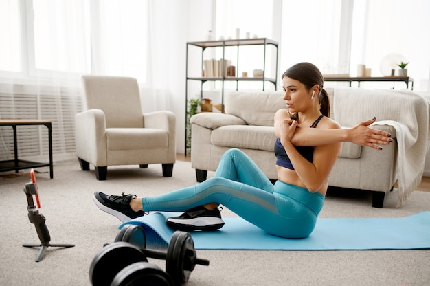 Lächelndes mädchen sitzt auf dem boden zu hause, online-fitnesstraining am laptop. weibliche person in sportbekleidung, internet-sporttraining, rauminnenraum