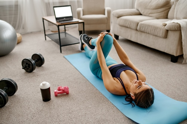 Lächelndes mädchen sitzt zu hause auf dem boden, online-fit-training am laptop. weibliche person in sportbekleidung, internet-sporttraining, rauminnenraum