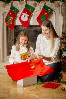 Lächelndes mädchen und mutter, die weihnachtsgeschenke in rotes papier einwickeln und mit goldenem band binden