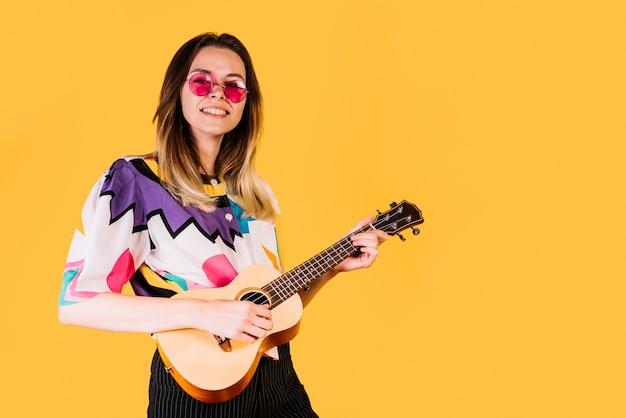 Lächelndes mädchen, welches die ukulele spielt