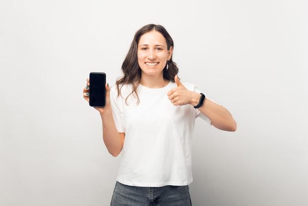 Lächelndes mädchen zeigt der kamera die gleiche geste und den bildschirm ihres telefons.