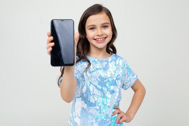 Lächelndes mädchen zeigt einen leeren bildschirm mit einem modell auf einem weißen