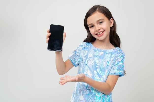 Lächelndes mädchen zeigt einen leeren telefonbildschirm mit einem modell auf einem weiß mit kopierraum