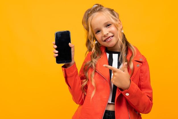 Lächelndes mädchen zeigt einen telefonbildschirm mit einem modell auf einem gelben hintergrund.