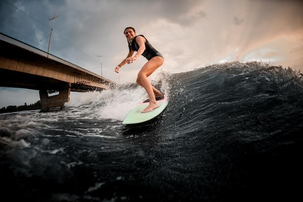 Lächelndes mädchenreiten auf dem wakeboard auf dem fluss im hintergrund der enormen brücke