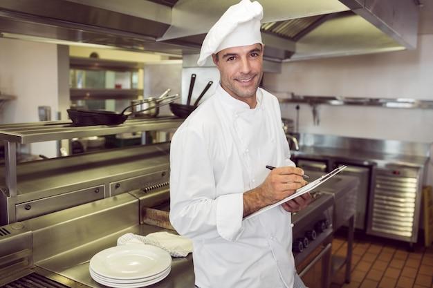 Lächelndes männliches kochschreiben auf klemmbrett in der küche