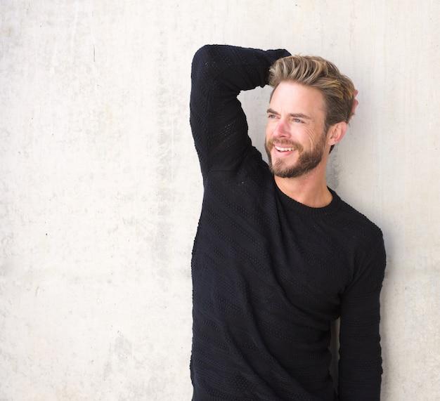 Lächelndes männliches mode-modell, das in der schwarzen strickjacke aufwirft